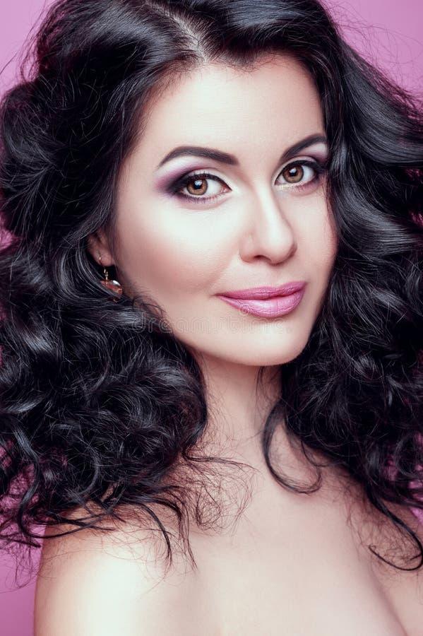 Mulher moreno bonita com um cabelo agradável da composição e das ondas imagens de stock royalty free
