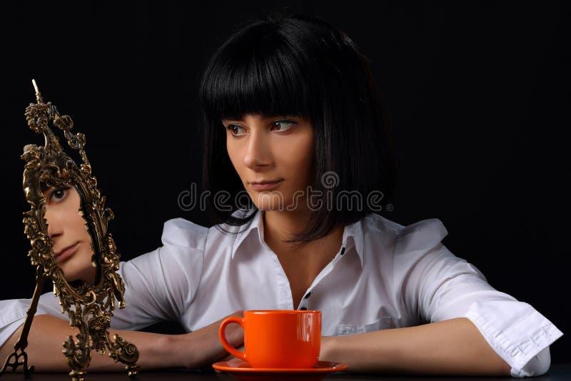 Mulher moreno bonita com uma xícara de café e um espelho velho imagem de stock