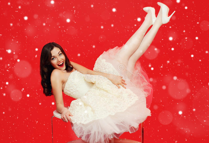 Mulher moreno bonita da noiva do Natal no vestido de casamento branco que tem o divertimento na tabela sobre o fundo vermelho col fotografia de stock