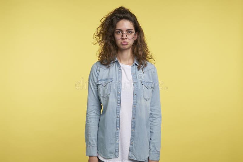 A mulher moreno bonita desagradada faz uma cara decepcionante engraçada, isolada sobre o fundo amarelo imagens de stock