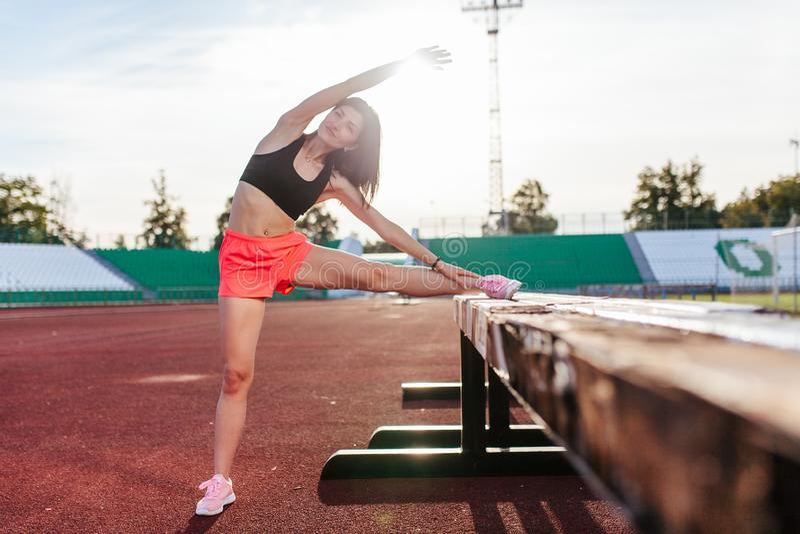 Mulher moreno bonita do corredor que faz o esticão inclinando seu pé na barreira para o esticão de corrida antes do exercício - t imagens de stock