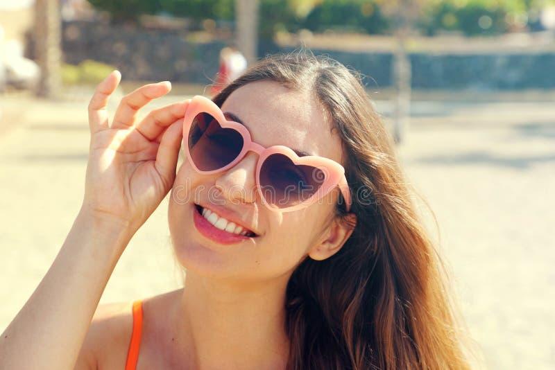 Mulher moreno bonita em óculos de sol cor-de-rosa do lolita do coração na praia Feriados, curso das f?rias e conceito da liberdad imagens de stock