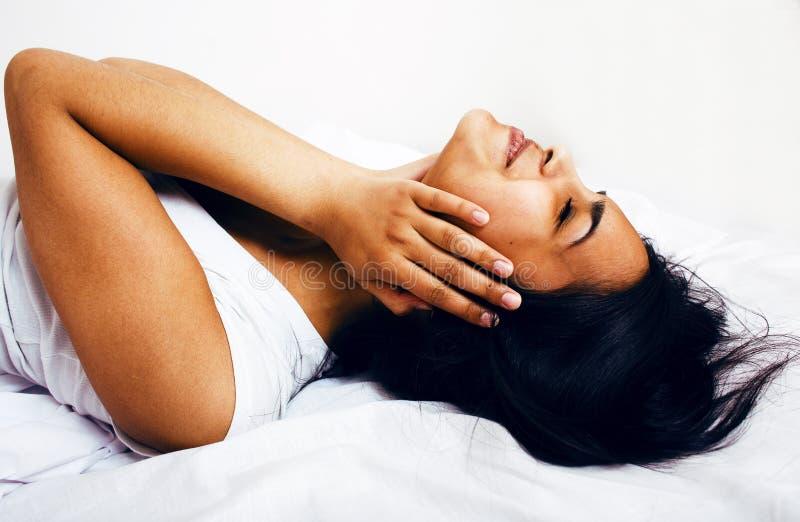 Mulher moreno bonita na cama, sono chanfrado, dor de cabeça imagens de stock