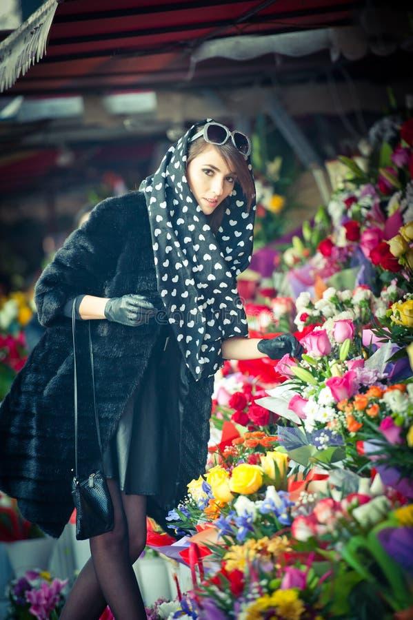 Mulher moreno bonita no preto na loja de florista fotografia de stock
