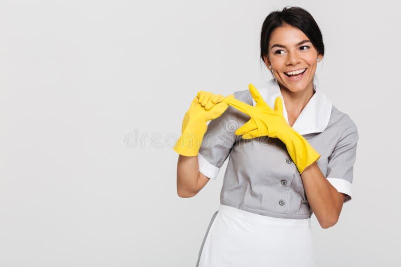 Mulher moreno bonita no uniforme cinzento que descola seu prot amarelo foto de stock royalty free