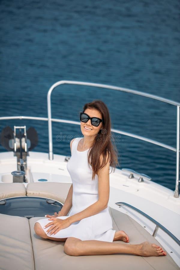 Mulher moreno bonita no vestido branco que levanta no barco fotografia de stock royalty free