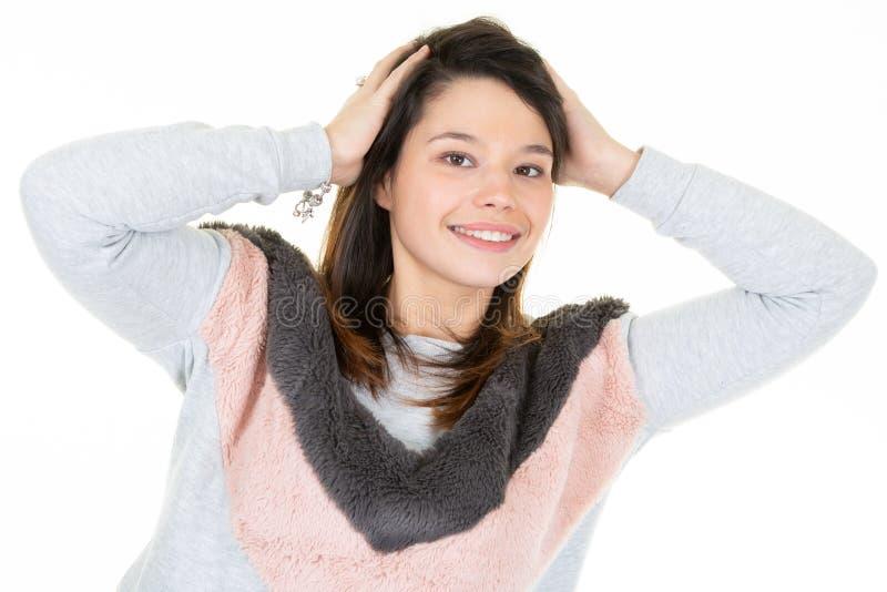 Mulher moreno bonita nova na consideração e nos sorrisos brancos do fundo à câmera fotos de stock
