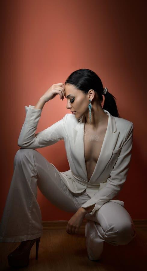 Mulher moreno bonita nova no terno branco elegante com assento da calças Menina sedutor que levanta, tiro do cabelo escuro do est imagem de stock royalty free