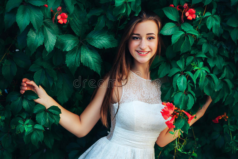 A mulher moreno bonita nova no vestido branco está no fundo da parede com folhas e as flores verdes fotos de stock royalty free