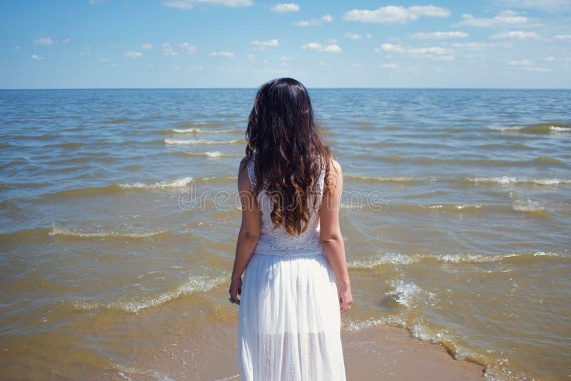 Mulher moreno bonita nova no vestido branco no litoral fotos de stock royalty free