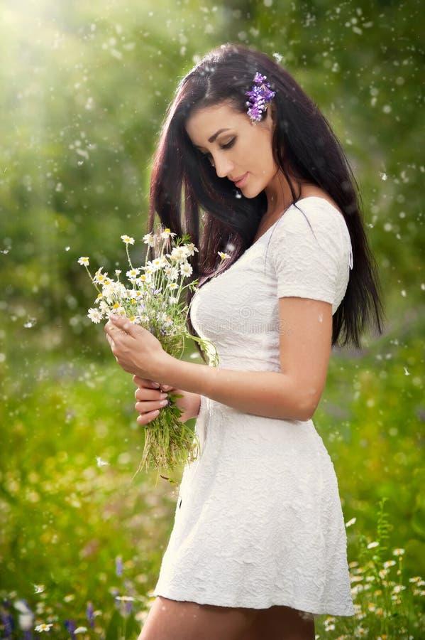 Mulher moreno bonita nova que guarda um ramalhete das flores selvagens em um dia ensolarado Retrato da fêmea longa atrativa do ca fotografia de stock royalty free