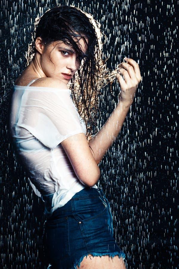 Mulher moreno bonita nova que levanta na roupa elegante molhada fotos de stock