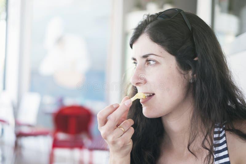 Mulher moreno bonita que come microplaquetas no restaurante fotos de stock