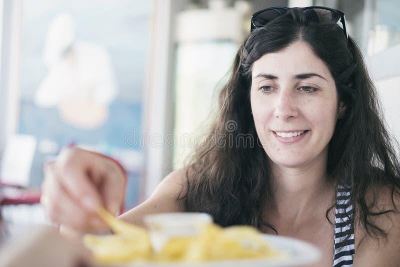 Mulher moreno bonita que come microplaquetas no restaurante fotografia de stock