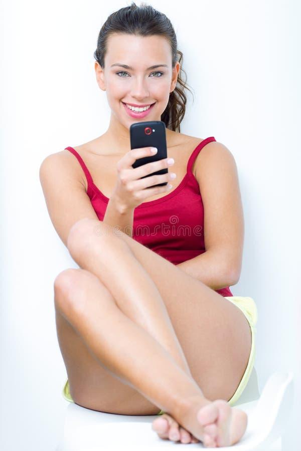 Mulher moreno bonita que olha o móbil