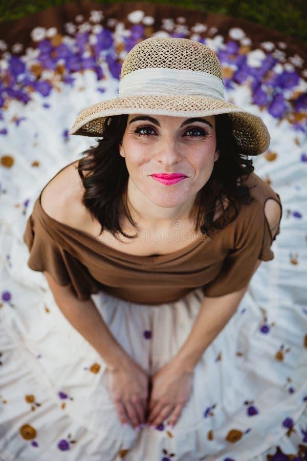 Mulher moreno bonita que senta-se com uma saia florescida Vista da fotografia de stock