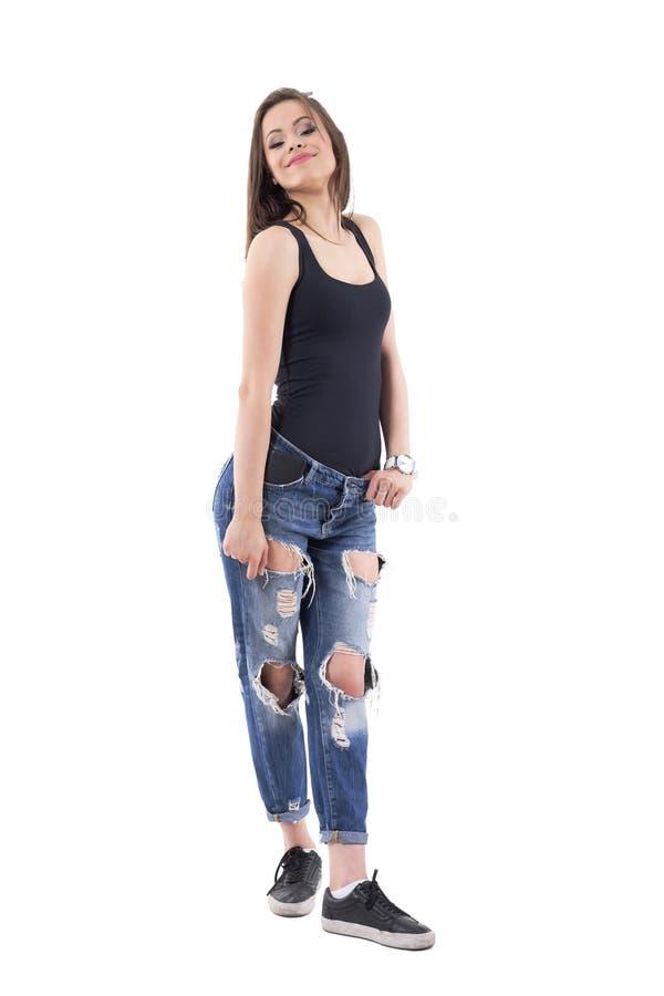 Mulher moreno bonito da beleza que levanta com cabeça para trás e braços para baixo em calças de brim rasgadas foto de stock