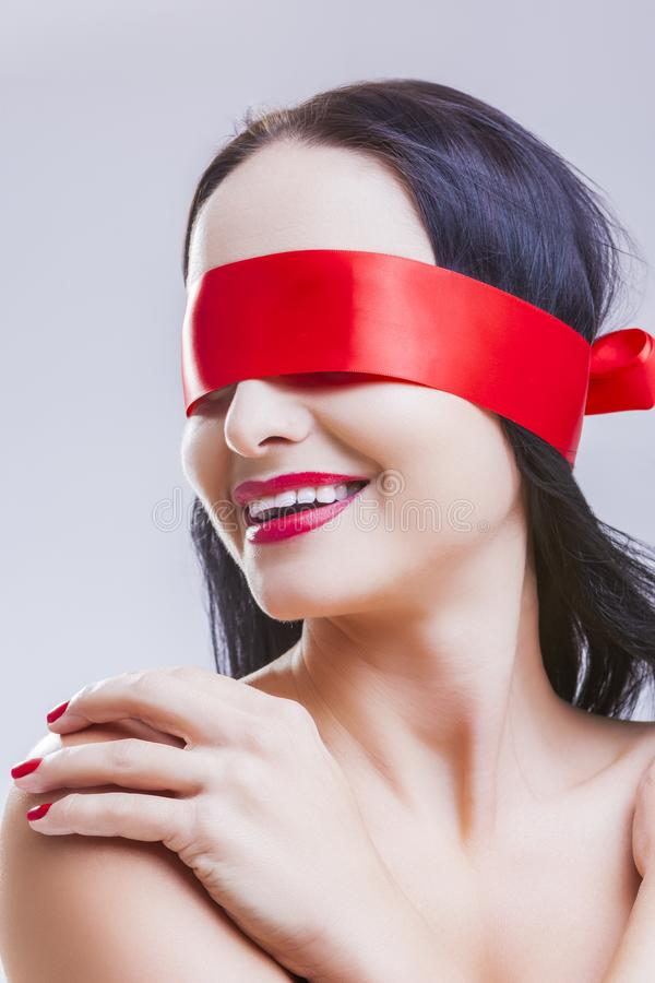 Mulher moreno caucasiano que levanta com os antolhos vermelhos da fita nos olhos fotos de stock royalty free