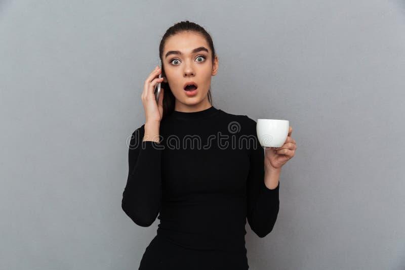 Mulher moreno chocada na roupa preta que fala pelo smartphone foto de stock