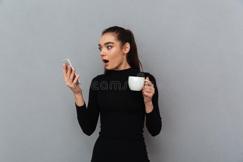 Mulher moreno chocada na roupa preta que olha o smartphone fotografia de stock