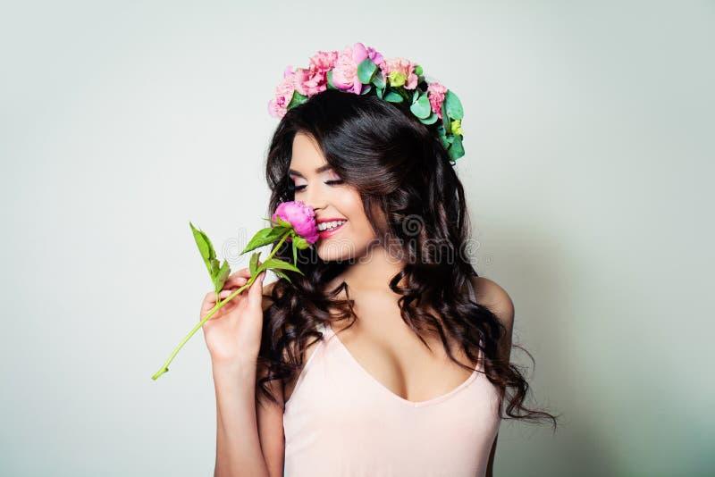 Mulher moreno com as flores longas do cabelo encaracolado e da mola fotografia de stock royalty free