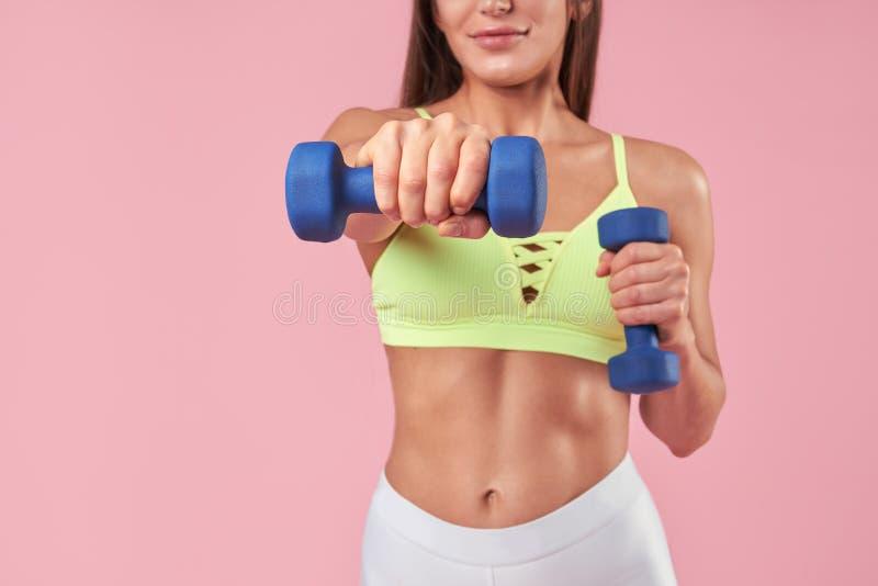 Mulher moreno com corpo muscular no treinamento da roupa dos esportes e exercício fazer com os sinos do dumm no fundo cor-de-rosa fotografia de stock