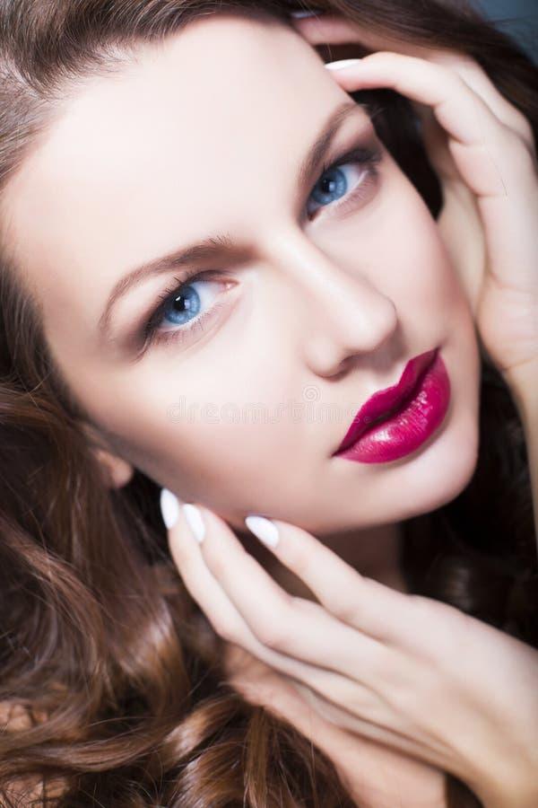 A mulher moreno com olhos azuis sem compõe, pele e as mãos sem falhas naturais perto de sua cara fotos de stock royalty free