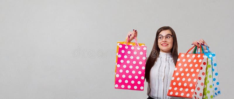 A mulher moreno com packeges nas mãos em um backgroun cinzento imagens de stock