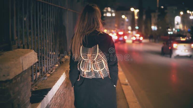 Mulher moreno com trouxa que anda tarde na noite A menina atrativa atravessa o centro de cidade perto da estrada na noite foto de stock