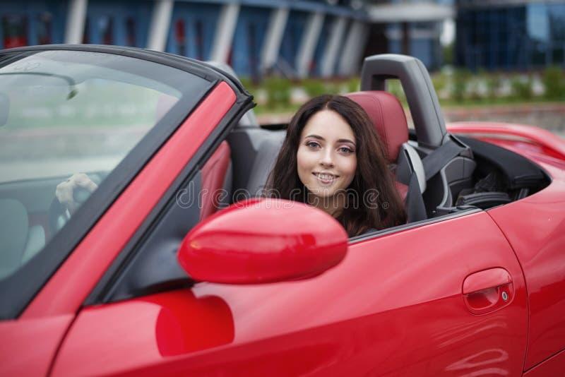 Mulher moreno consideravelmente nova que conduz o carro vermelho luxuoso do cabriolet imagens de stock royalty free