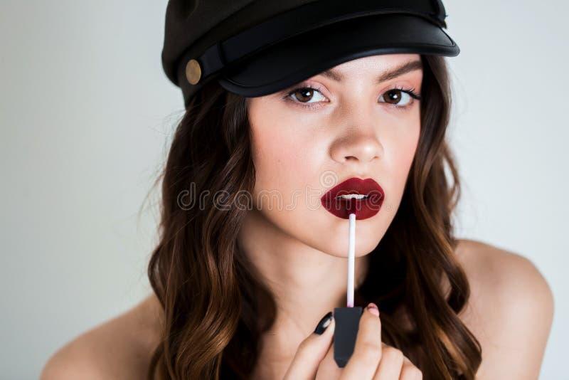 Mulher moreno consideravelmente nova sedutor que usa a escova do bordo para aplicar o batom vermelho a seus bordos Batom da propa imagens de stock royalty free