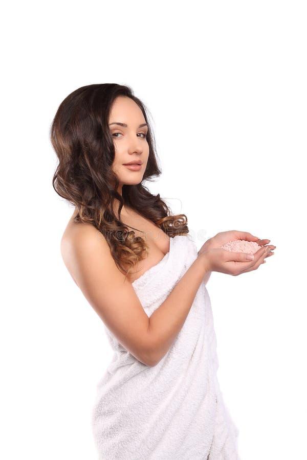 Mulher moreno da beleza que guarda o sal para banhar-se, o retrato bonito da menina com cabelo encaracolado e a toalha branca Con fotografia de stock