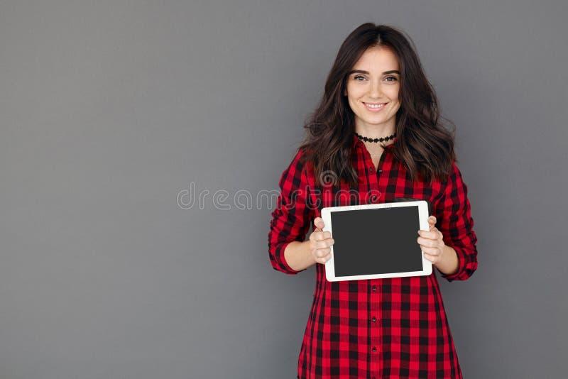 A mulher moreno de sorriso apresenta sua tabuleta imagem de stock