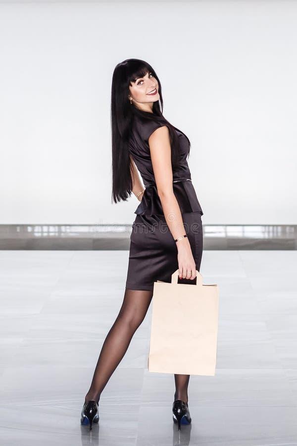 Mulher moreno de sorriso atrativa nova vestida em um terno de negócio preto que guarda o saco de compras do papel, andando em uma fotos de stock royalty free