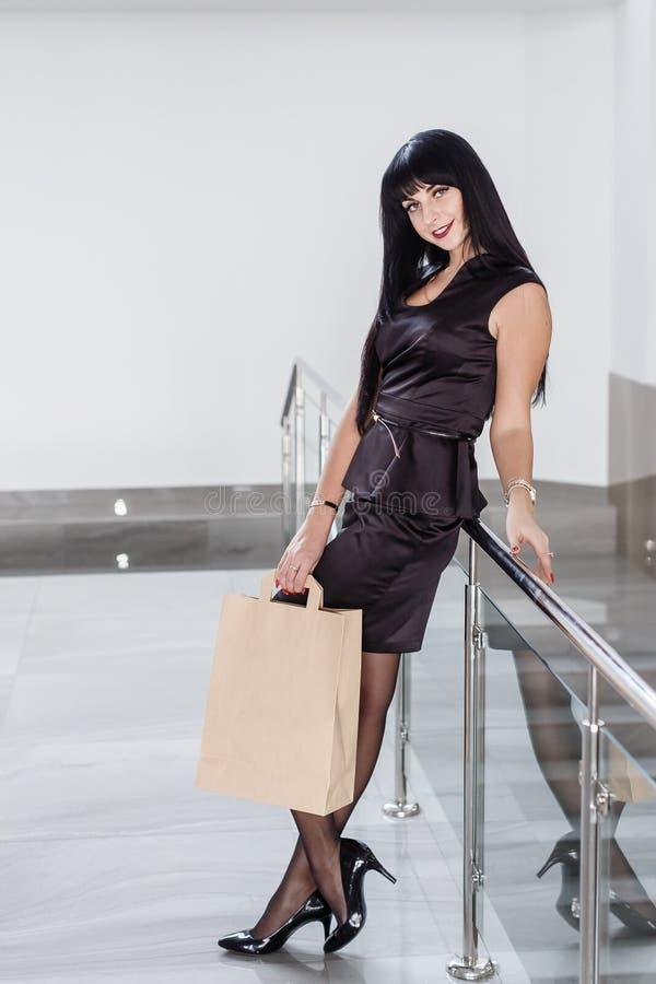 Mulher moreno de sorriso atrativa nova vestida em um terno de negócio preto que guarda o saco de compras do papel, andando em uma foto de stock