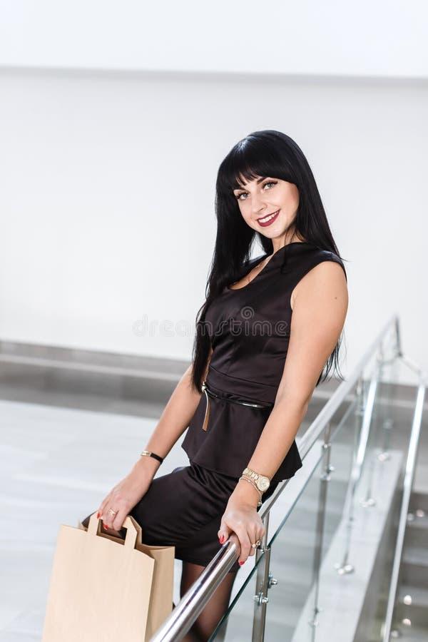 Mulher moreno de sorriso atrativa nova vestida em um terno de negócio preto que guarda o saco de compras do papel, andando em uma imagem de stock