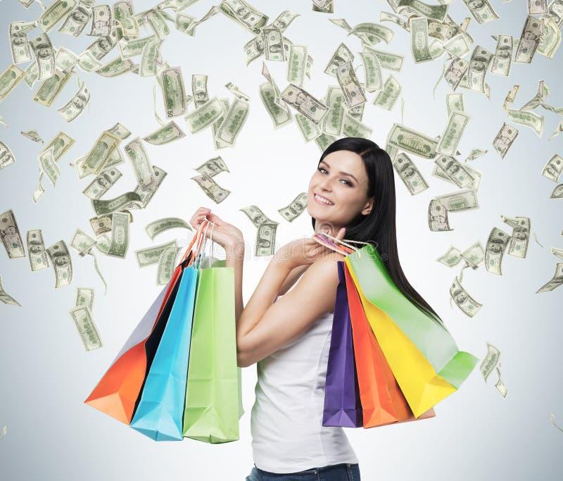 Mulher moreno de sorriso bonita com os sacos de compras coloridos das lojas extravagantes imagem de stock