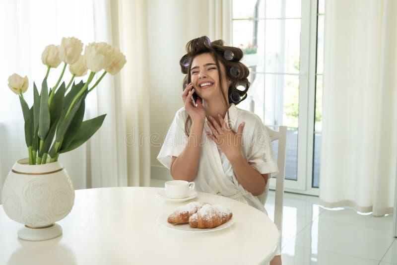 Mulher moreno de sorriso nova bonita nos encrespadores de cabelo que falam no smartphone ao beber o café e comer imagens de stock royalty free