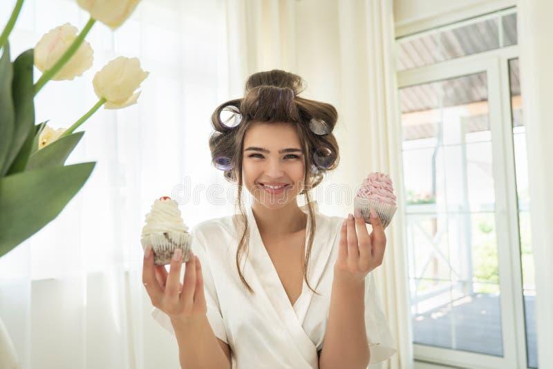 Mulher moreno de sorriso nova bonita nos encrespadores de cabelo que guardam dois queques em ambas as mãos que estão na cozinha b fotos de stock