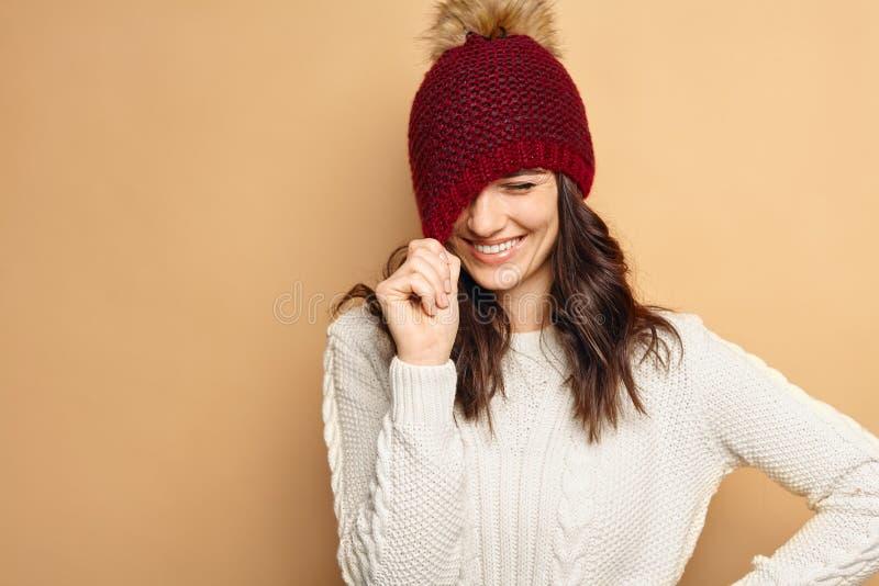 A mulher moreno de sorriso parecendo jovem natural bonita, lenço feito malha vestindo, coberto com a neve lasca-se inverno nevand fotografia de stock royalty free