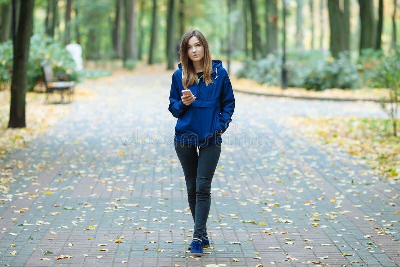 A mulher moreno desportiva à moda em urbano na moda outwear o levantamento no parque da cidade da floresta no dia chuvoso frio da imagem de stock royalty free