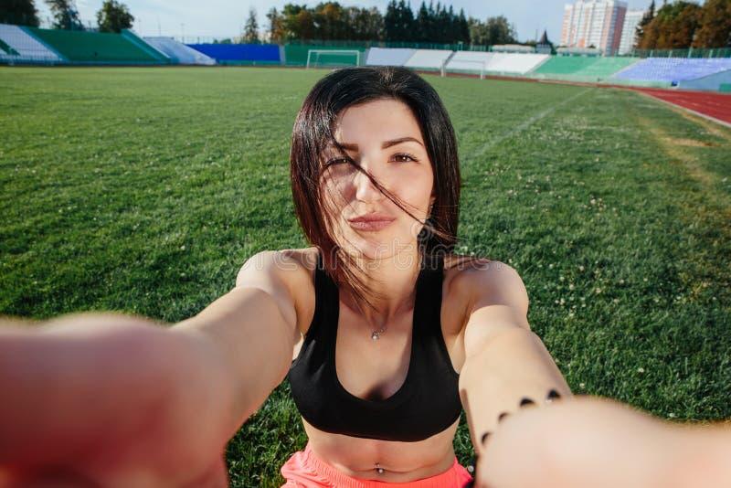 Mulher moreno desportiva nova no short e selfie fazendo superior, fim da cara do sorriso acima no gramado de um estádio de futebo imagens de stock royalty free