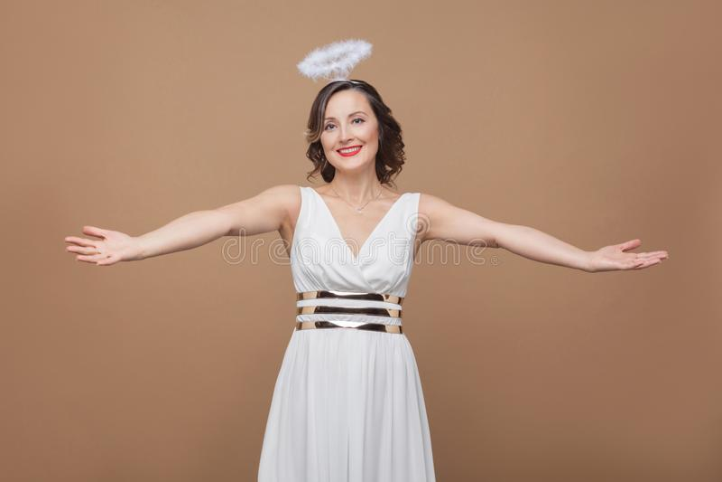A mulher moreno elegante envelhecida meio do anjo no vestido branco quer a fotos de stock