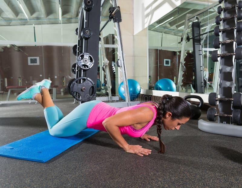 A mulher moreno em joelhos do gym levanta a flexão de braço foto de stock