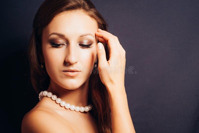 Mulher moreno em um close-up escuro do fundo fotografia de stock royalty free