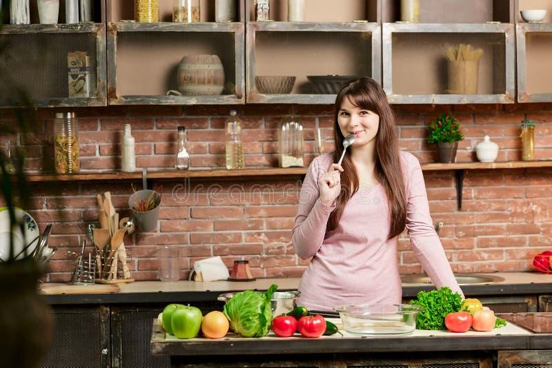 A mulher moreno em um revestimento cor-de-rosa está na cozinha perto de uma tabela com legumes frescos e lambe uma colher fotos de stock