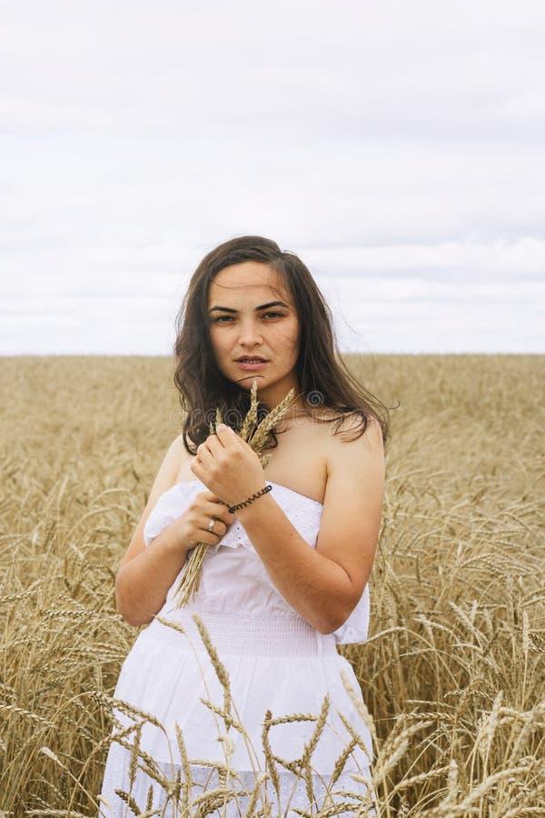 Mulher moreno em um vestido branco em um campo imagens de stock royalty free