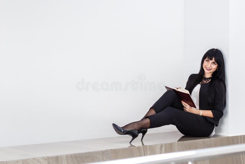 Mulher moreno feliz atrativa nova que mantém um caderno vestido em um terno de negócio preto que senta-se em um assoalho em um es imagens de stock royalty free