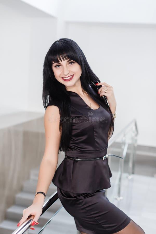 A mulher moreno feliz atrativa nova vestida em um terno de negócio preto com uma saia curto está estando contra a parede branca d fotografia de stock