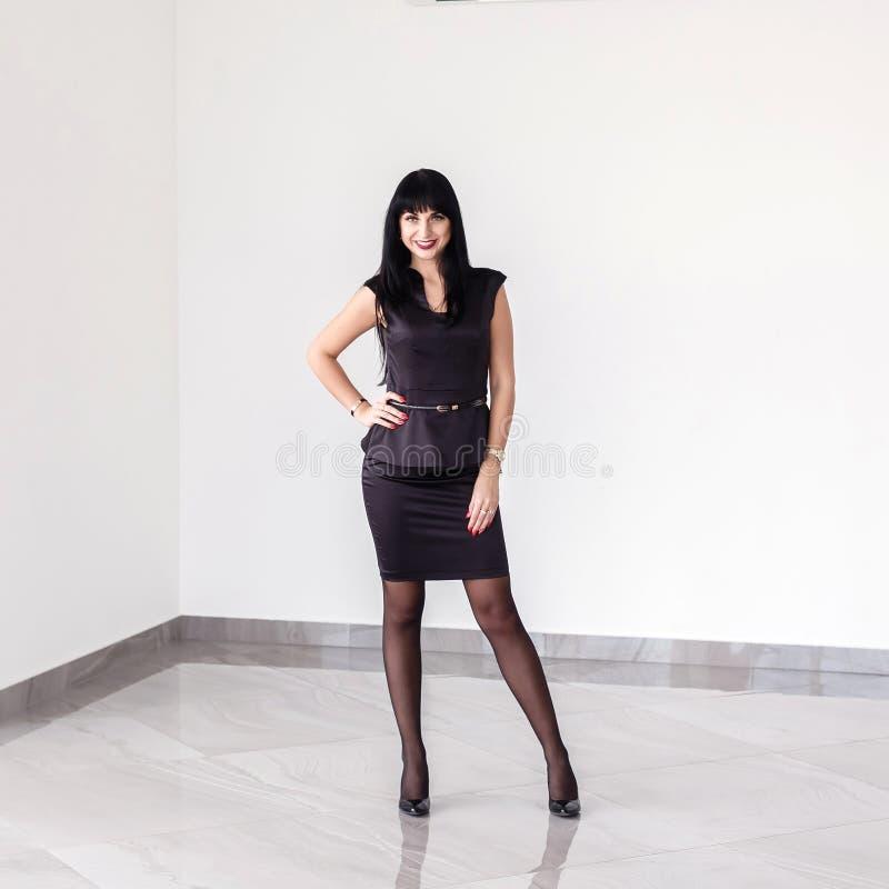 A mulher moreno feliz atrativa nova vestida em um terno de negócio preto com uma saia curto está estando contra a parede branca d fotos de stock royalty free